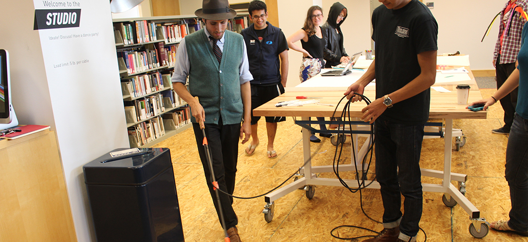 Carmen tests a cane with audio—hooked up to an amplifier and microphone, it now senses and