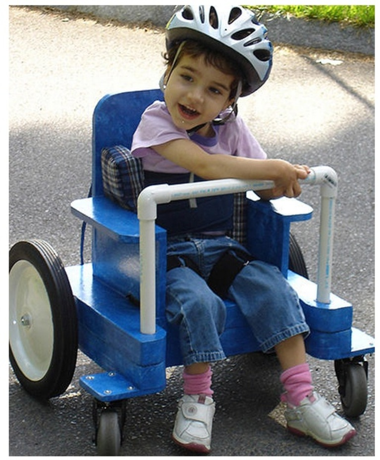 A child rides an adaptive wheeled riding toy, made of cardboard and PVC pipe.