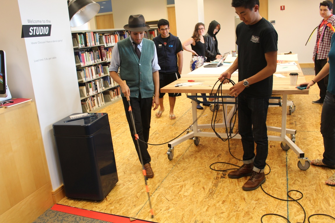 Carmen tests out the amped cane with students looking on.