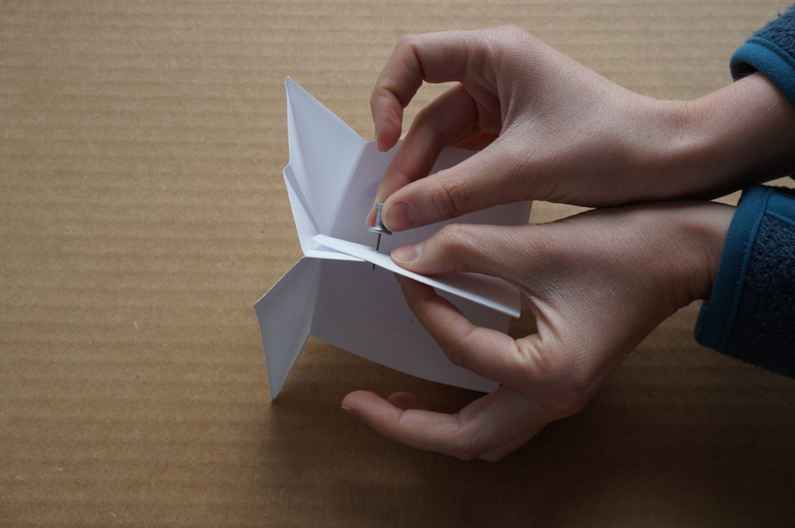 Two hands hold a paper sketch model for a lectern, testing its geometry and folding logic.