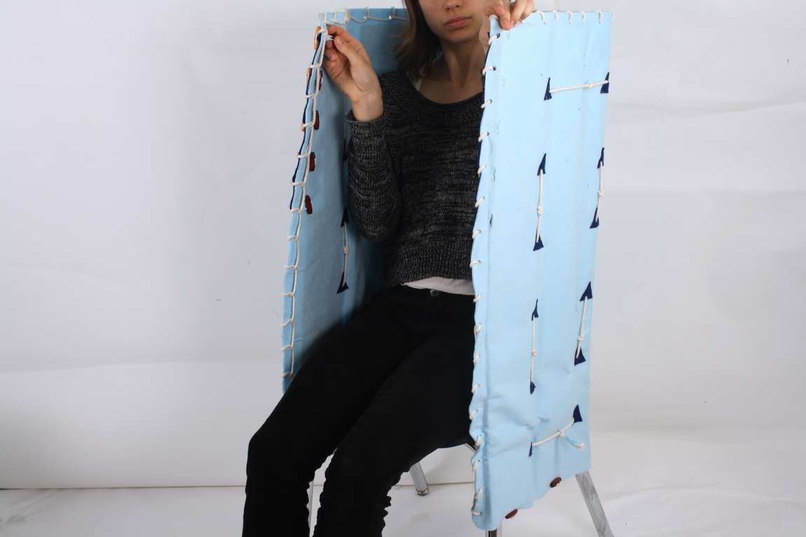 An Olin student models sitting in the chair with felted canopy drawn close, the height of which would provide total coverage for a school-age child.