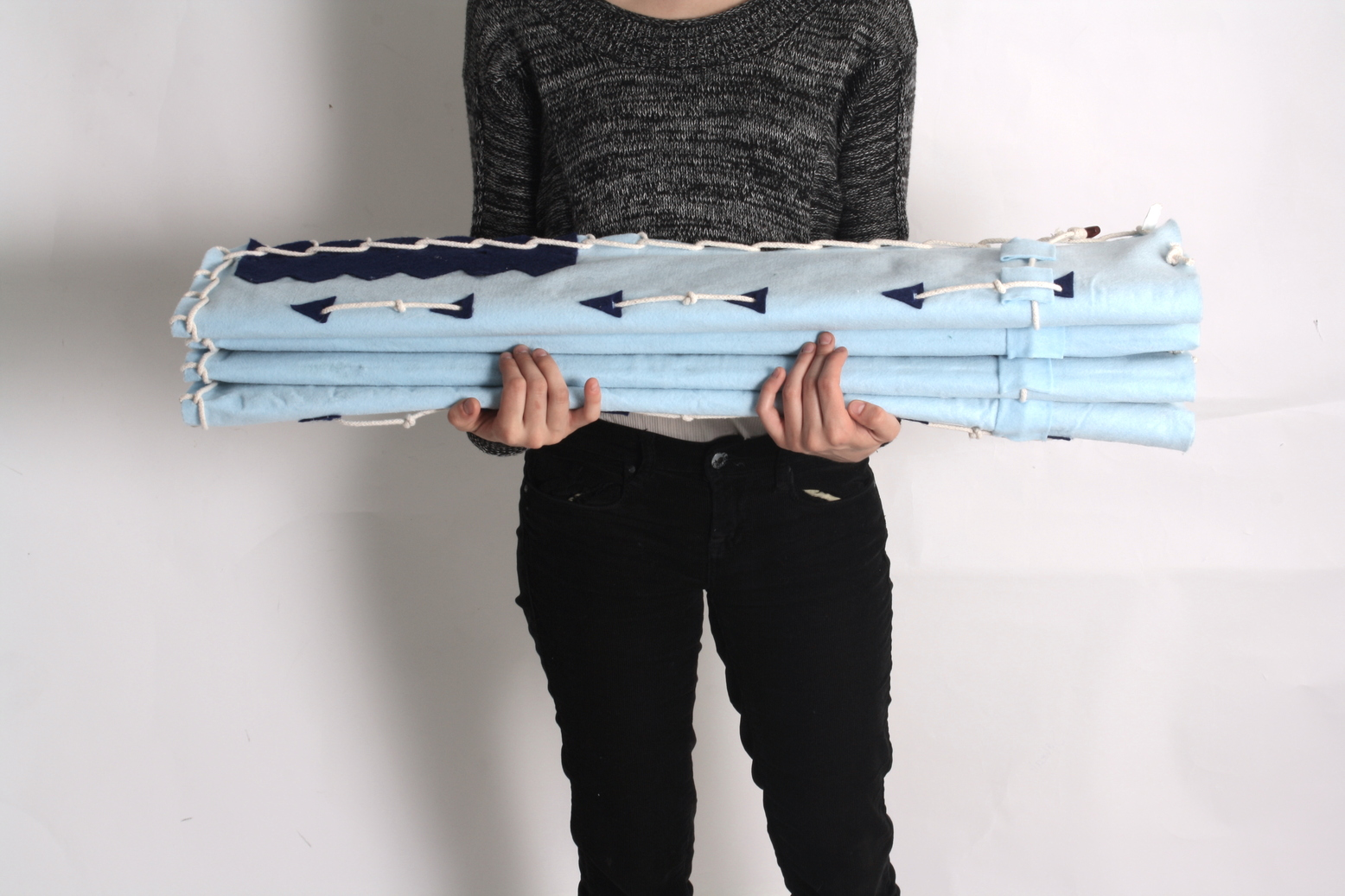 A student holds a foldable, accordion-style fabric